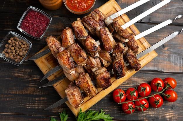 Costolette di agnello alla griglia su tagliere su spiedino con spezie e salsa. vista dall'alto sul tavolo di legno scuro dark