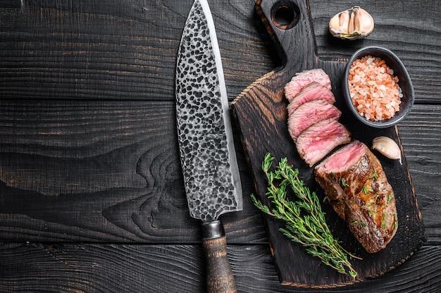 Bistecca di carne di filetto di agnello alla griglia su una mannaia