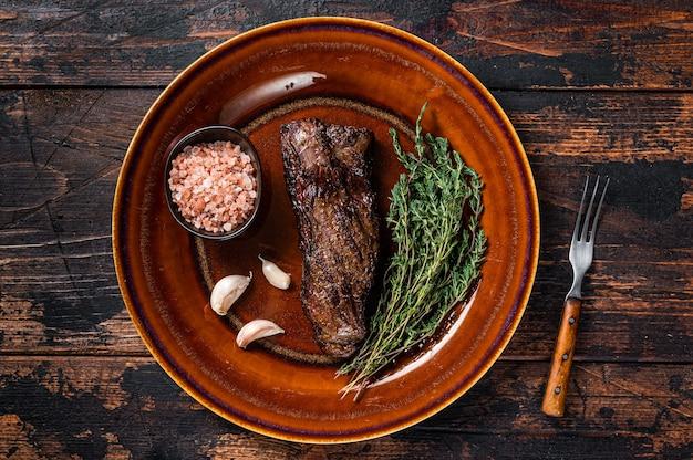 Bistecca di manzo alla griglia machete gonna su piatto rustico con erbe e sale rosa
