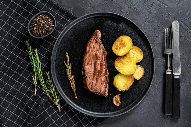 Bistecca di manzo marinata alla griglia. sfondo nero. vista dall'alto. Foto Premium
