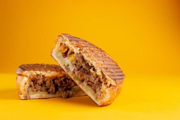 Panino di carne alla griglia su sfondo giallo. banner orizzontale