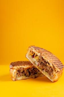 Panino di carne alla griglia su sfondo giallo. banner verticale