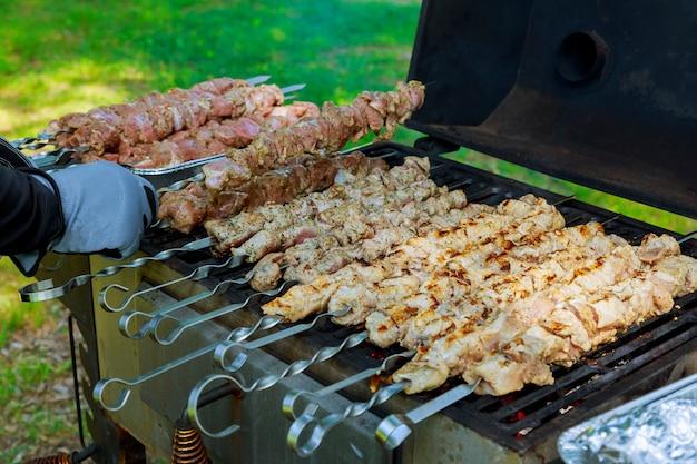 Barbecue con spiedini di carne arrostita alla griglia. sfondo di carne churrasco barbeque.