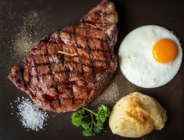 Bistecca di carne alla griglia e purè di patate con sale e un uovo su superficie scura