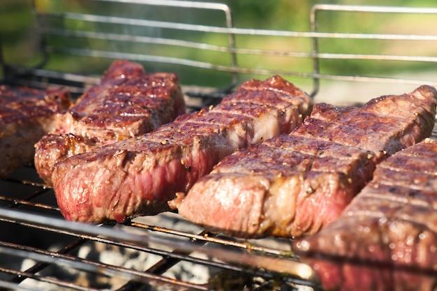 Carne alla griglia su una griglia. bistecche alla brace su braciere con fumo naturale. cucinare all'aperto.