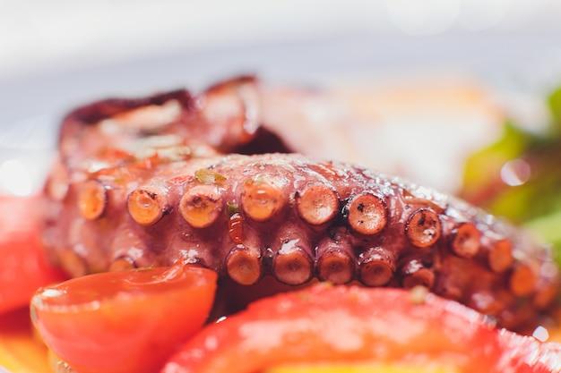 Polpo alla griglia con verdure e salsa di seppie. ristorante, lifestyle, cibo da viaggio - polpo alla griglia con verdure menu del ristorante. frutti di mare freschi italiani.