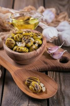 Olive alla griglia con aglio, olio d'oliva e spezie su fondo di legno rustico