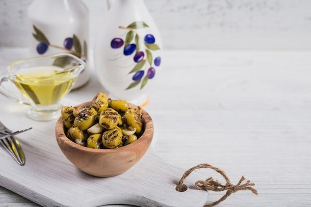 Olive alla griglia con aglio, olio d'oliva e spezie su fondo di legno rustico bianco