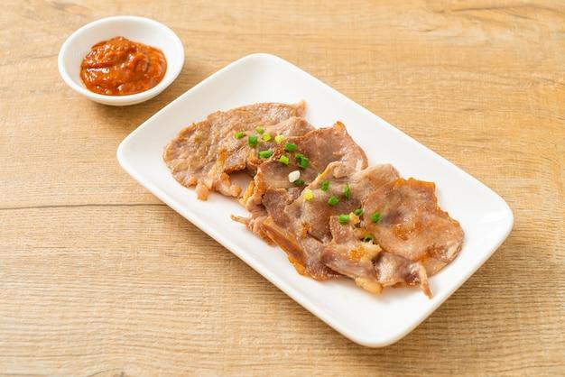 Collo di maiale alla griglia affettato su piatto in stile asiatico