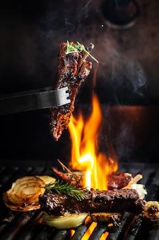Costolette di maiale alla griglia tagliate su una forchetta contro il fuoco