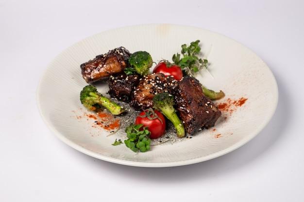 Costine di maiale alla griglia in glassa di miele con pomodori e broccoli su una superficie bianca