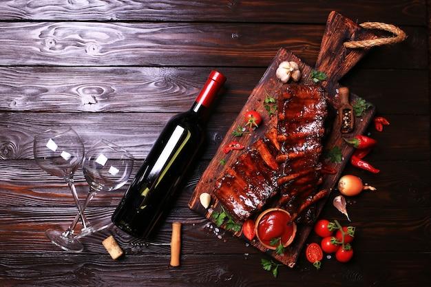Costolette di maiale alla griglia con bottiglia di spezie e verdure di vino rosso su fondo di legno