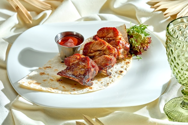 Costine di maiale alla griglia con pane pita e salsa rossa. costolette bbq in un piatto bianco.