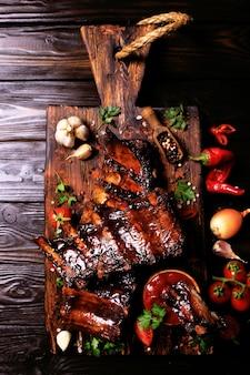 Costolette di maiale alla griglia con spezie e verdure su fondo di legno