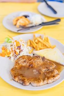 Bistecca di maiale alla griglia wit patatine fritte sul piatto
