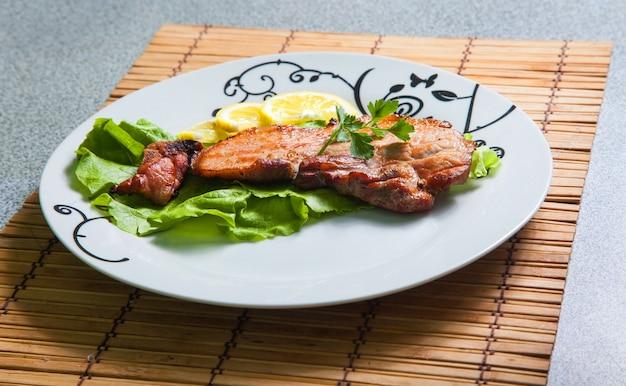 Maiale alla griglia con limone e insalata sulla piastra