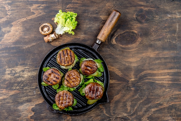 Hamburger arrostiti del fungo del panino di portobello sulla griglia del ghisa ob di legno, vista superiore