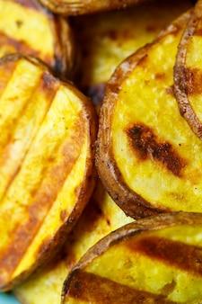 Patate grigliate fino a doratura in un piatto blu su sfondo giallo