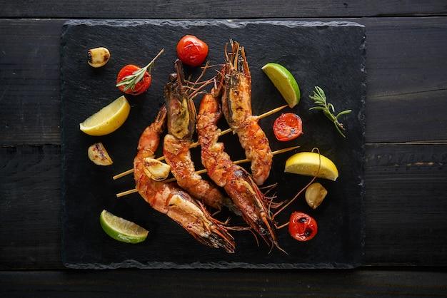 Gamberi alla griglia con ingredienti piccanti aglio e pomodoro sul tavolo di legno scuro