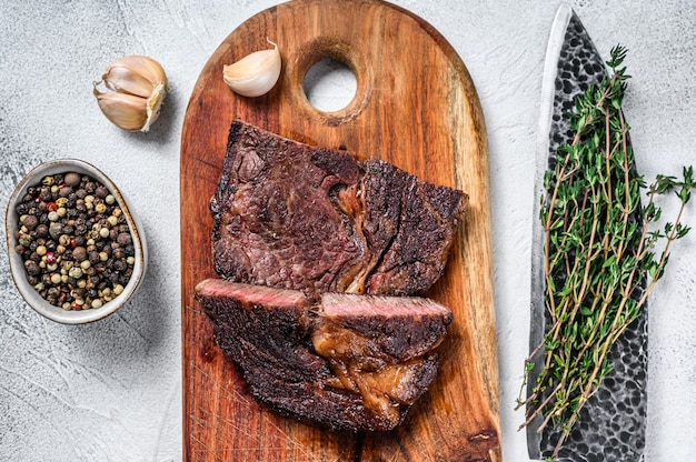 Bistecca di manzo di manzo alla griglia su un tagliere di legno
