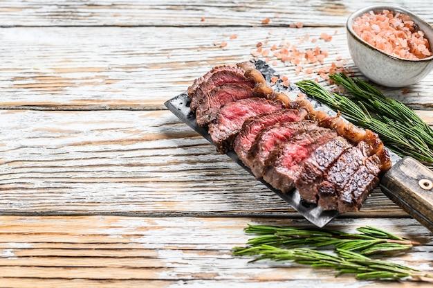 Bistecca alla griglia su una mannaia di carne. vista dall'alto bianco. copia spazio.