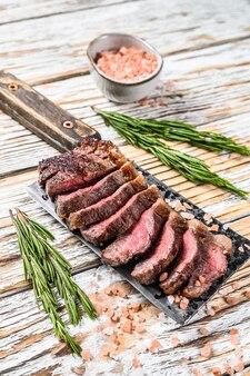 Bistecca alla griglia su una mannaia di carne. fondo in legno bianco. vista dall'alto.