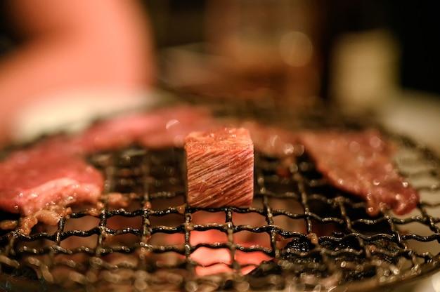 Fetta di manzo crudo alla griglia su griglia a carbone ardente