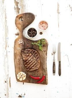 Bistecca di manzo alla griglia con erbe e spezie sul tagliere di noce sulla superficie in legno rustico bianco