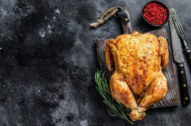 Pollo intero arrosto alla griglia. sfondo nero. vista dall'alto. copia spazio.