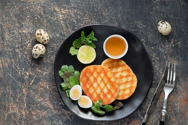 Fette rotonde grigliate di formaggio greco con miele, menta fresca e foglie di coriandolo. piatto disteso sul tavolo grigio scuro