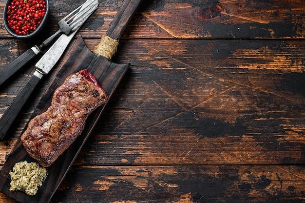 Bistecca di manzo black angus in marmo di scamone alla griglia. tavolo di legno. vista dall'alto.