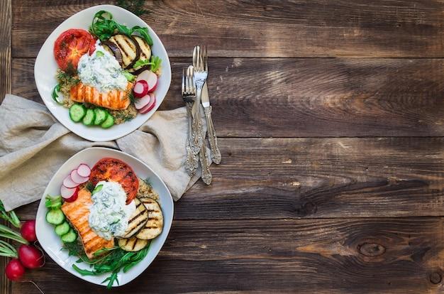 Melanzane e pomodori di salmone grigliati con quinoa e salsa tzatziki su fondo di legno rustico