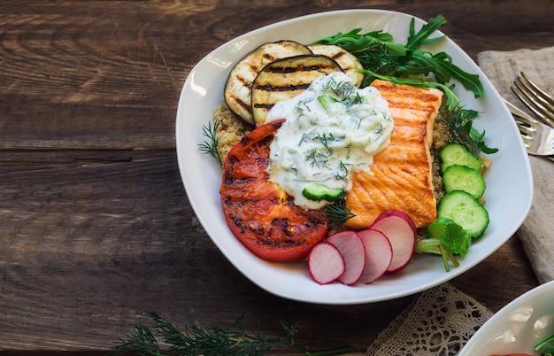 Salmone alla griglia, melanzane e pomodori con quinoa e salsa tzatziki su legno rustico. cena sana.