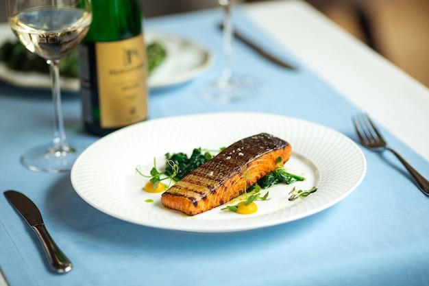 Bistecca di filetto di color salmone alla griglia sul tavolo blu servito