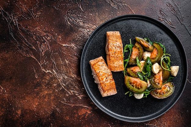 Bistecche di filetto di salmone alla griglia con rucola e insalata di pomodori su un piatto. sfondo scuro. vista dall'alto. copia spazio.