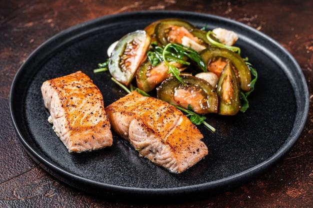 Filetto di salmone alla griglia bistecche con rucola e insalata di pomodori su un piatto. sfondo scuro. vista dall'alto.