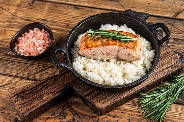 Bistecche di filetto di salmone alla griglia con riso bianco in padella. fondo in legno.
