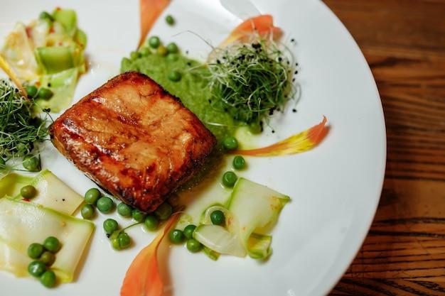 Filetto di salmone alla griglia con insalata su un piatto bianco.