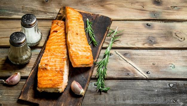 Filetto di salmone alla griglia con spezie ed erbe aromatiche sulla tavola di legno.