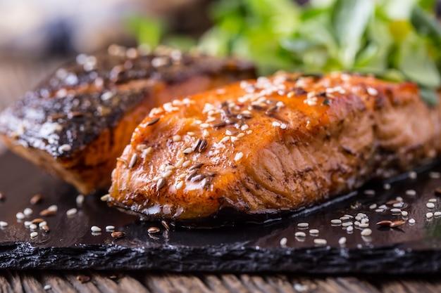 Filetti di salmone alla griglia con erbe su tavola di ardesia