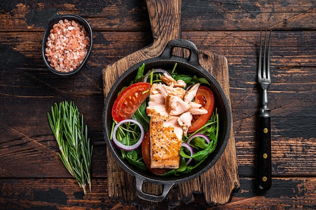 Filetto di salmone alla griglia con insalata fresca di rucola, avocado e pomodoro in padella