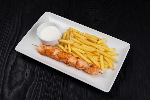 Shashlik di pesce salmone alla griglia con patate fritte e salsa su piatto bianco su fondo di legno nero