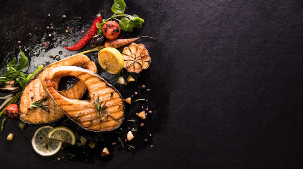 Pesce salmone alla griglia con condimento e verdure varie su fondo di pietra nera