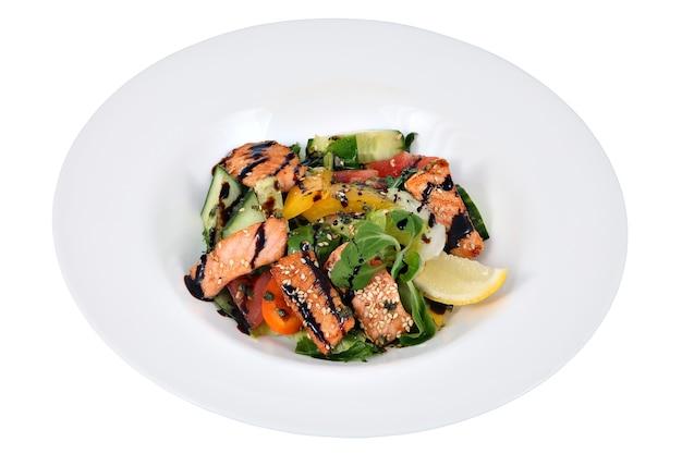 Insalata di salmone alla griglia in piatto rotondo in ceramica, isolato su sfondo bianco.