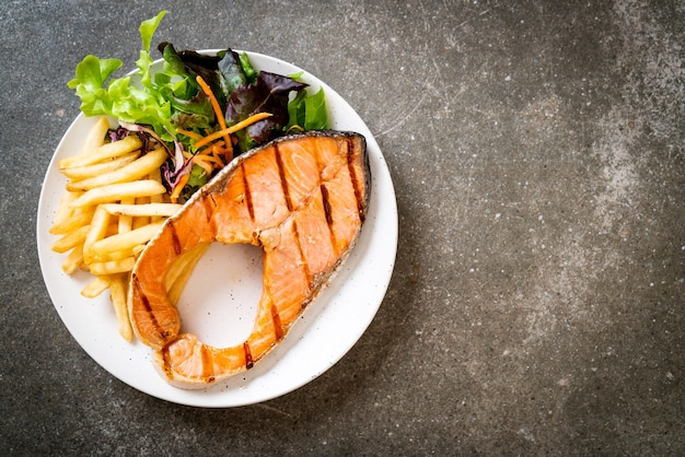 Filetto di bistecca di salmone alla griglia con verdure e patatine fritte sul piatto