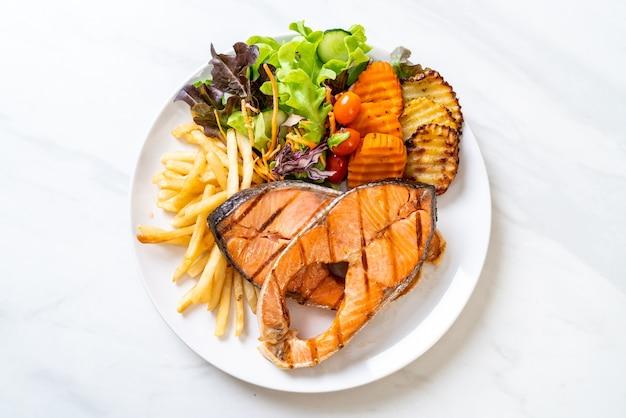 Filetto di bistecca di salmone alla griglia con verdure e patatine fritte Foto Premium