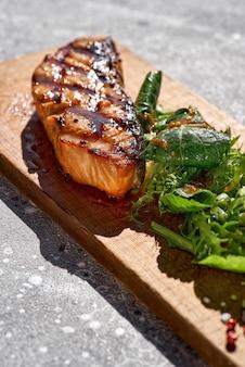 Bistecca di salmone alla griglia con barbecue, verdure fresche. filetto di pesce trota rossa barbecue decorato con verdure piccanti su pietra