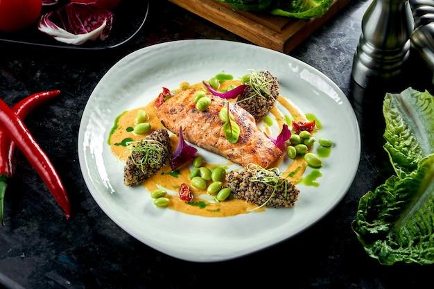 Trancio di salmone alla griglia con quinoa e fagiolini, salsa gialla, servito su un piatto bianco. cibo del ristorante. piatto di frutti di mare