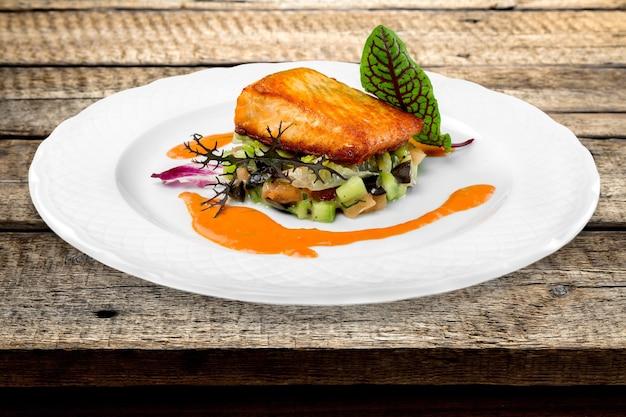 Trancio di salmone alla griglia con spinaci, crema tartara e spicchi di limone