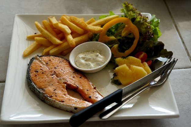 Trancio di salmone alla griglia con insalata di salsa al dragoncello e patatine fritte